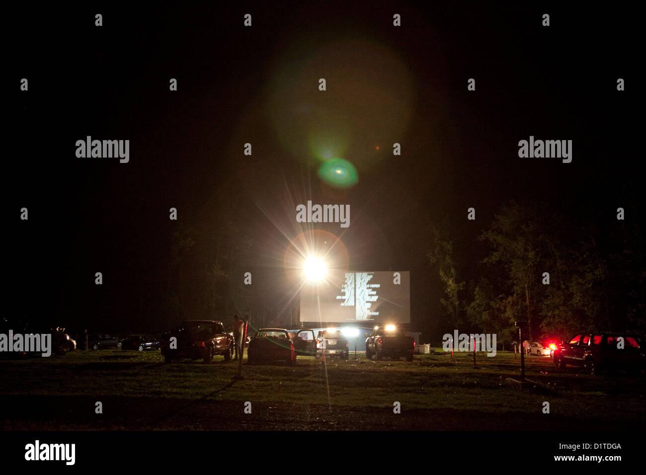 Nachtansicht der Abspann bei einer Fahrt im Film. Fahrzeuge abgestellt in Front, Lens Flare glänzt in Richtung Stockbild
