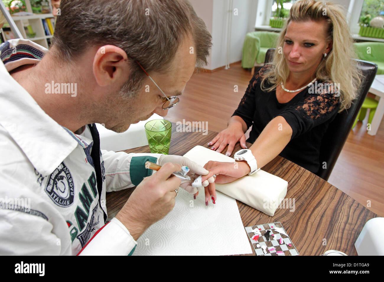 Berlin, Deutschland, verziert ein Nagel-Designer Nägel mit Airbrush ...