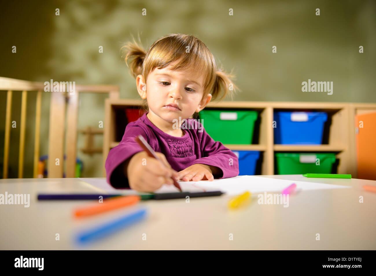 Kleines Mädchen, die Spaß an Schule und zeichnen mit Farben im kindergarten Stockbild