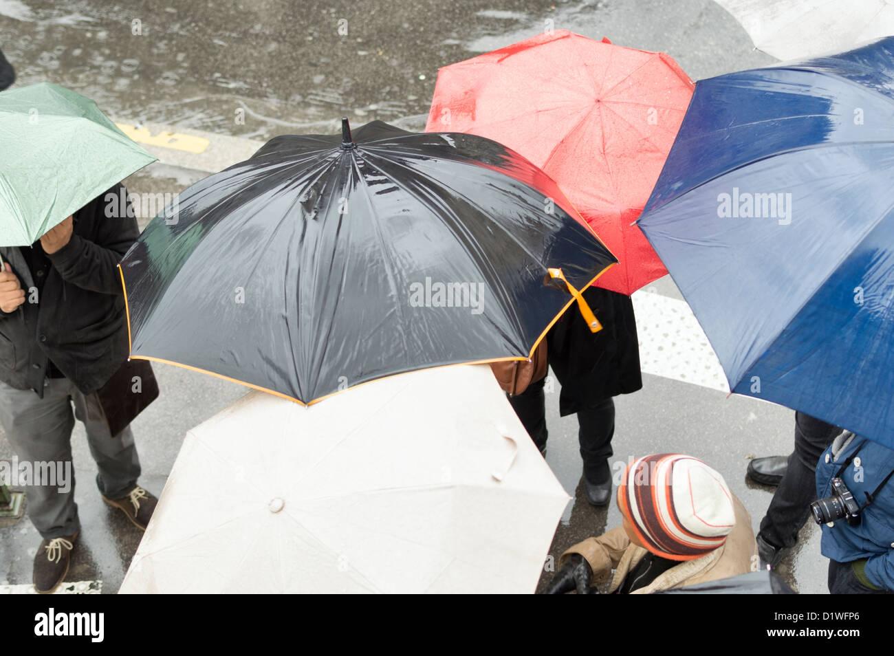 Paris, Frankreich: Touristen mit Sonnenschirmen auf einer Stadtstraße im Regen. Stockbild