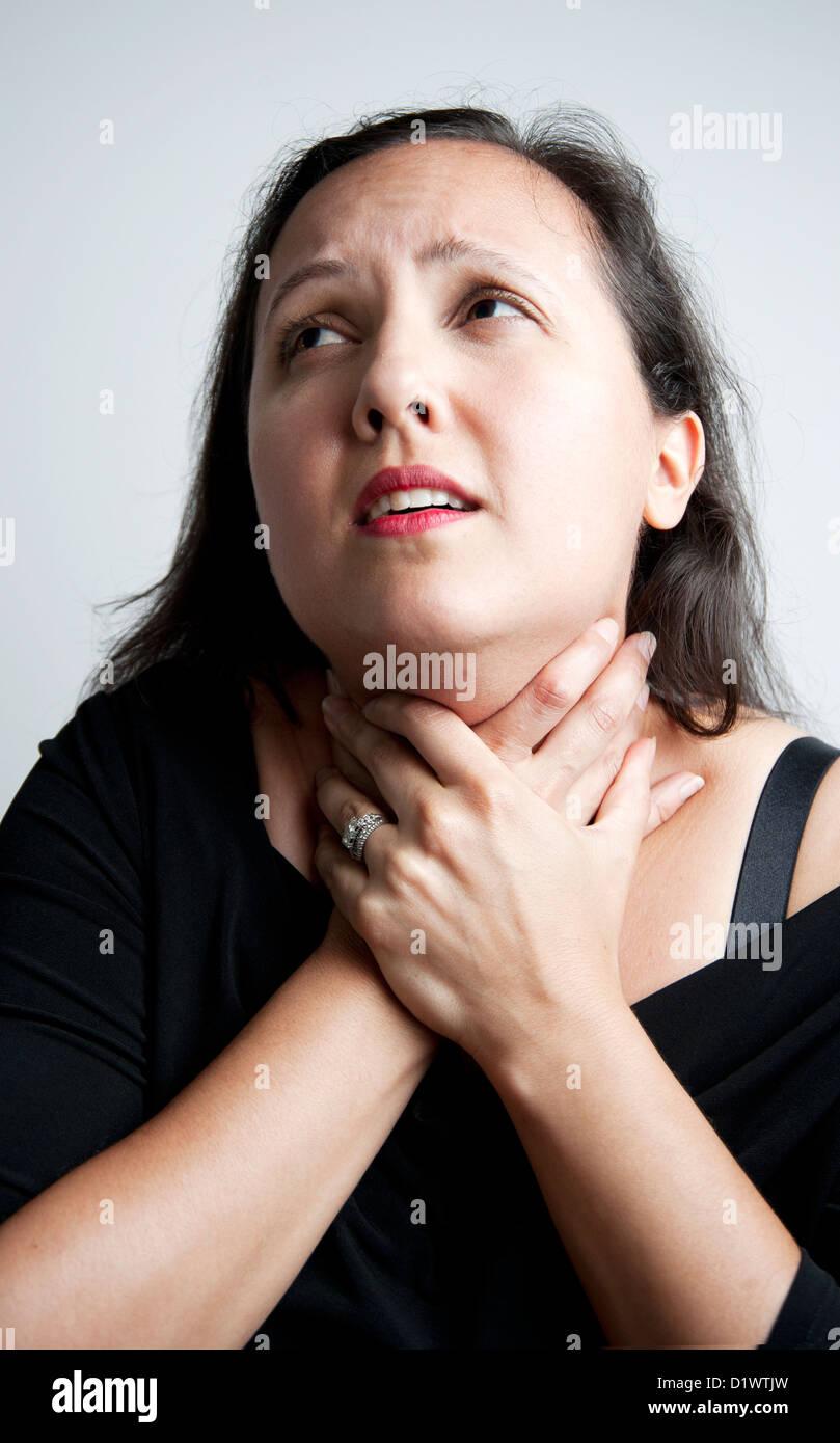 Eine Frau Schauspielerin greifen ihre eigenen Kehle auf sehr dramatische Weise Stockbild