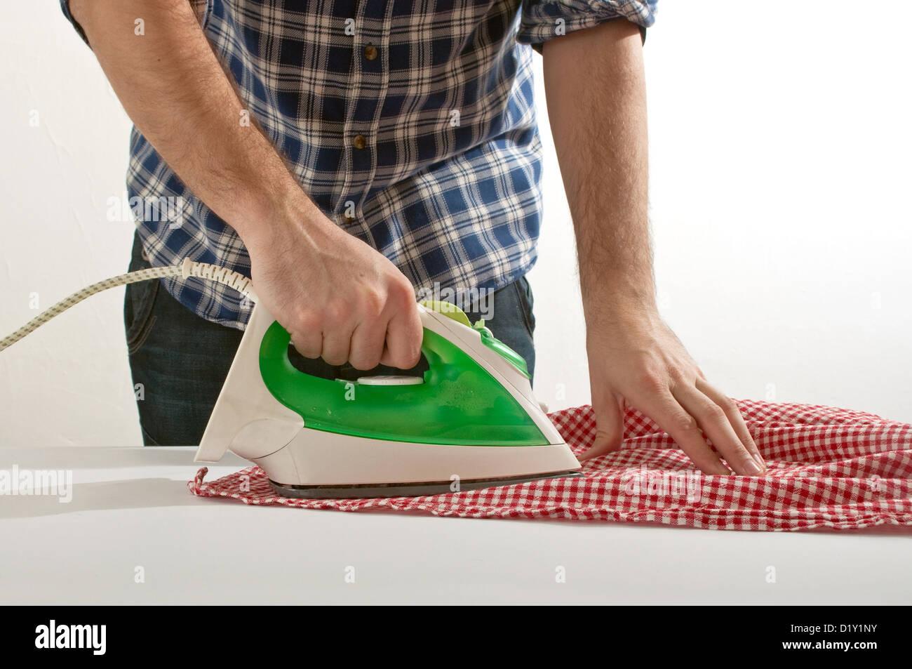 Mann eine rot-weiß karierte Tischdecke Bügeln Stockbild