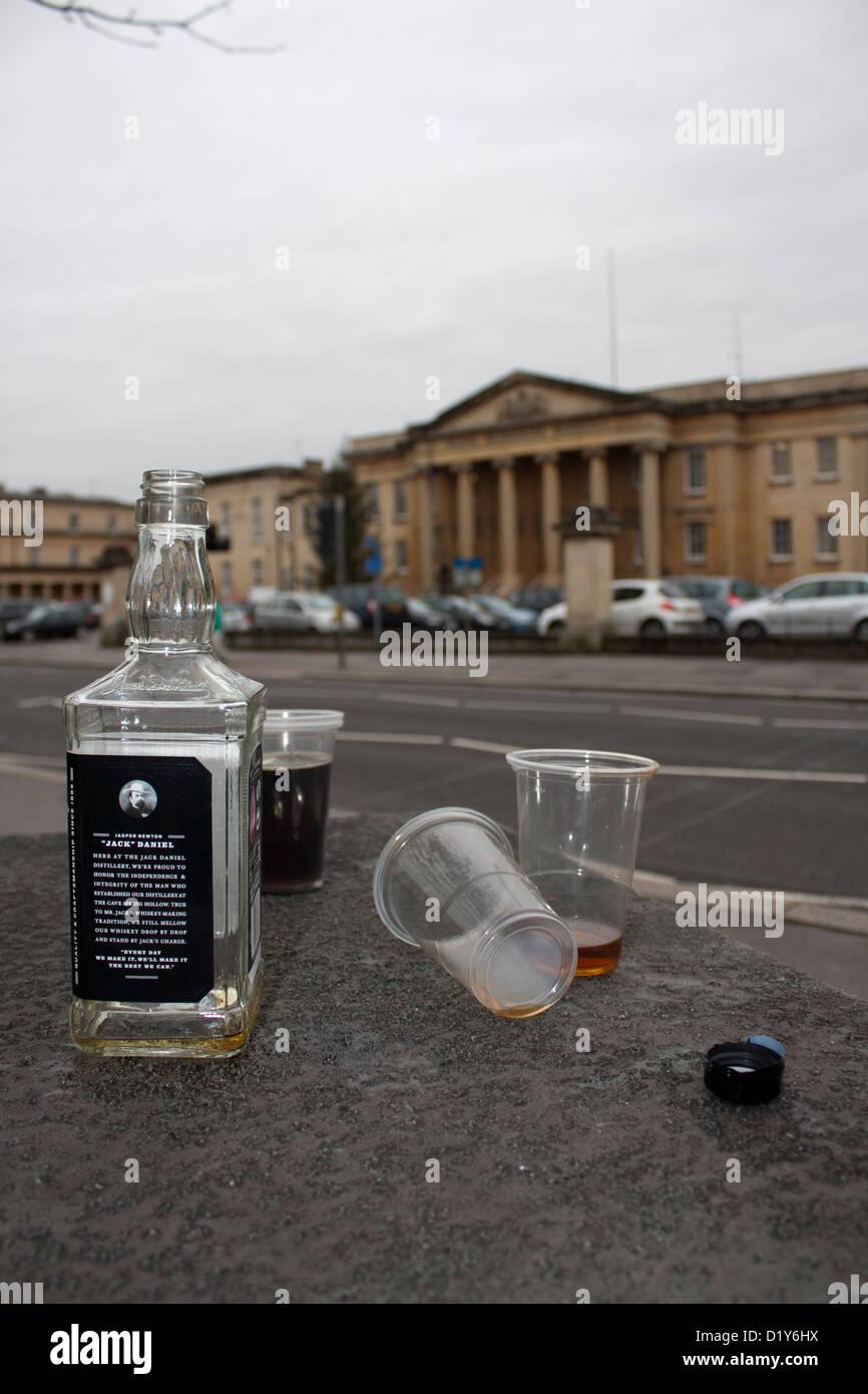 Eine leere verworfen Flasche Jack Daniels Bourbon Whisky und Gläser. Krankenhaus im Hintergrund. Healthcare Stockbild