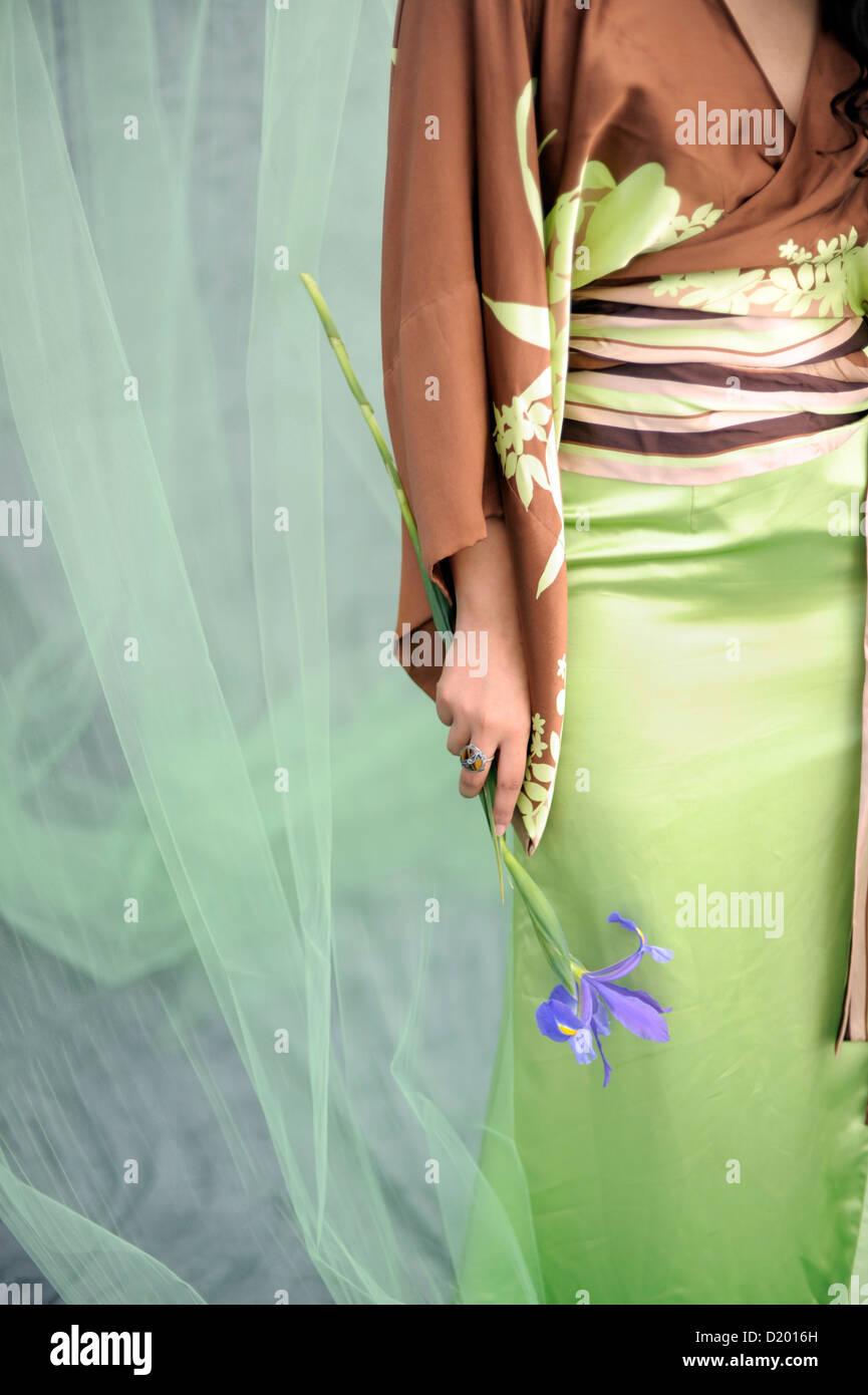 Anonyme Federmodells, die eine frische Iris Blume. Stockbild