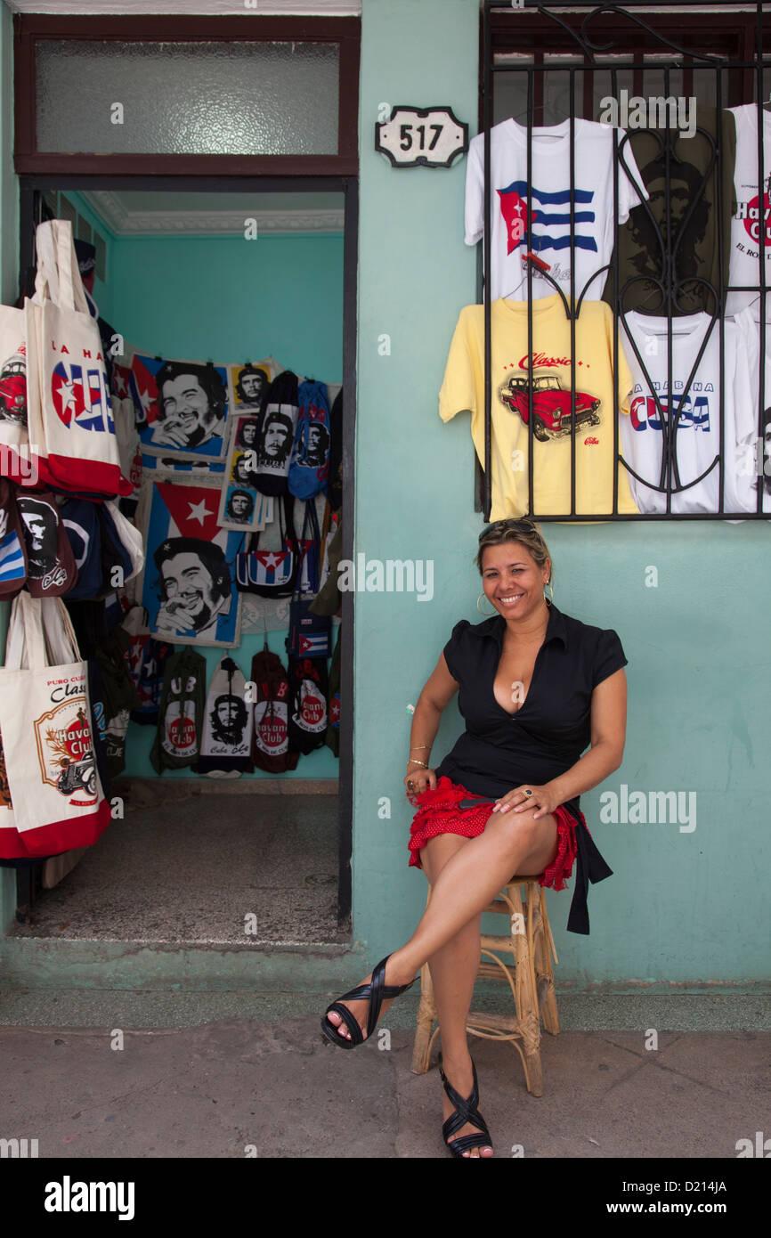 Frau vor einem Souvenirgeschäft mit Che Guevara Bild auf Produkte für Verkauf, Havana, Havanna, Kuba, Stockbild