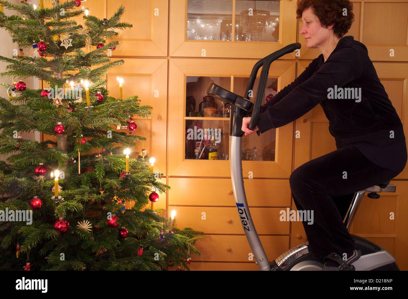 Frau mit Heimtrainer im Rahmen einer Silvester Auflösung, um fit zu ...