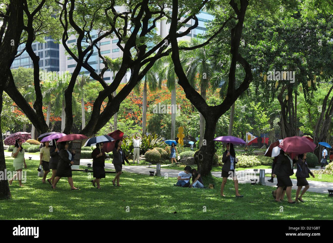 Frauen mit Sonnenschirmen, Ayala Triangle Park in Makati City, Insel Luzon, Philippinen, Asien Stockbild