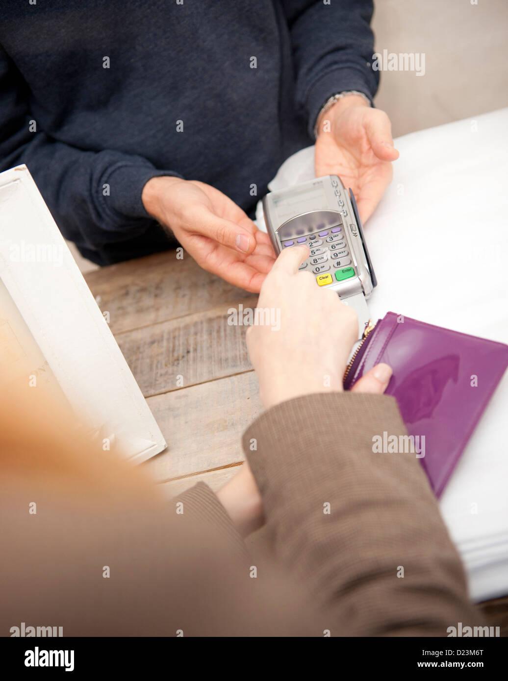 Ein Kunde, der Eingabe ihrer Pin-Nummer in Chip und Pin-Maschine Stockfoto