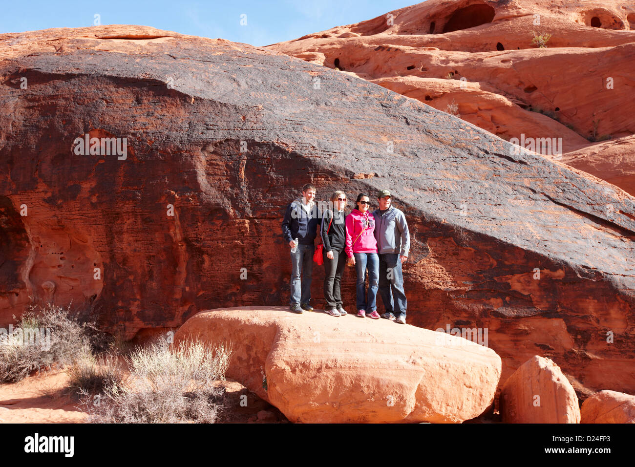 Touristen posieren vor Felsen bedeckt Petroglyphen durch Mäuse Tank Trail Tal des Feuers Staatspark Nevada, usa Stockfoto