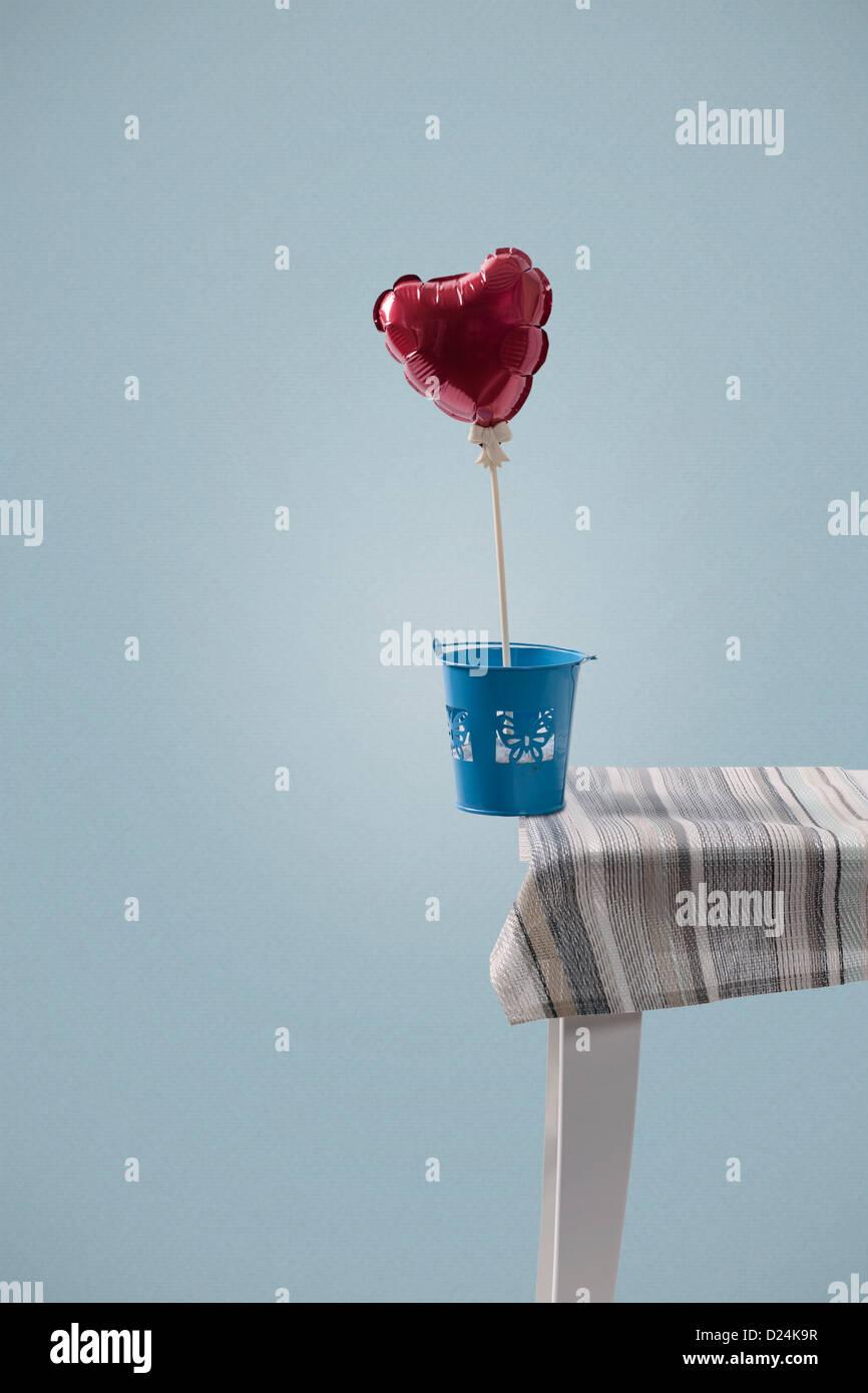 eine herzförmige Ballons auf die Tischkante ausgeglichen Stockfoto