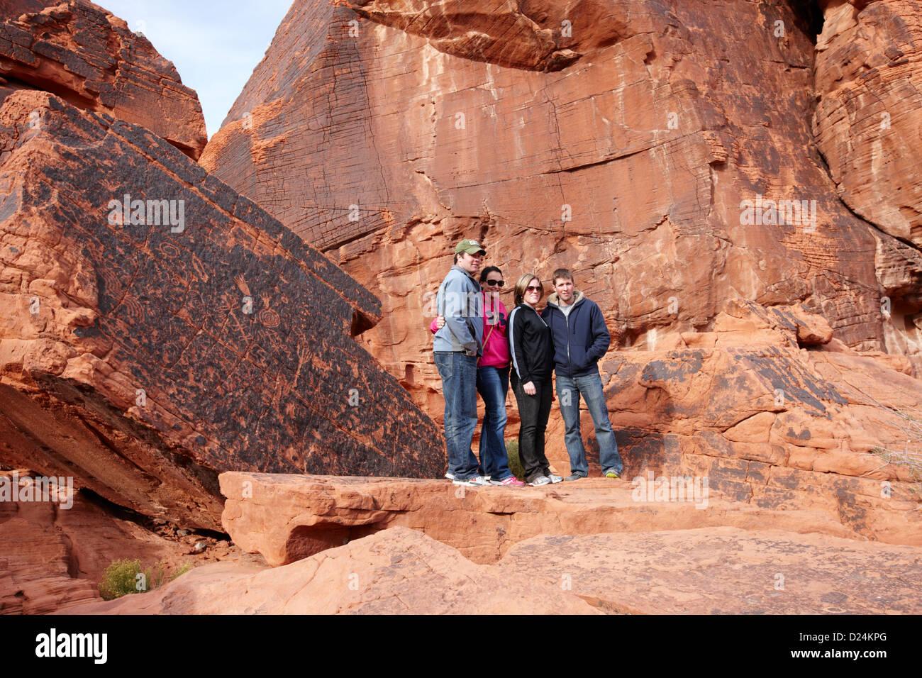 Touristen posieren vor Petroglyphen auf Atlatl großen Felsen Tal des Feuers Staatspark Nevada, usa Stockfoto