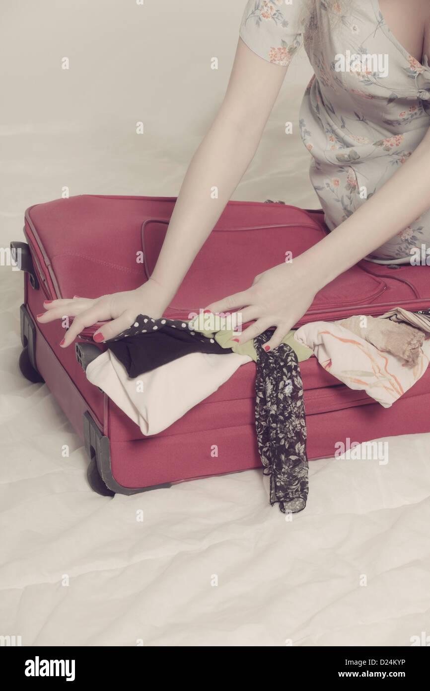 eine Frau versucht, einen Koffer zu schließen Stockbild
