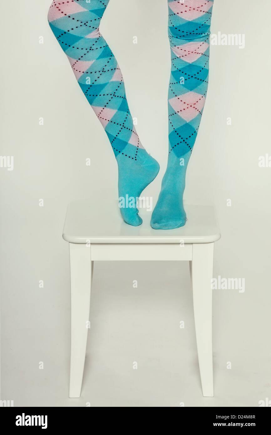 Beine einer Frau in Burlington Socken auf einem weißen Hocker Stockbild