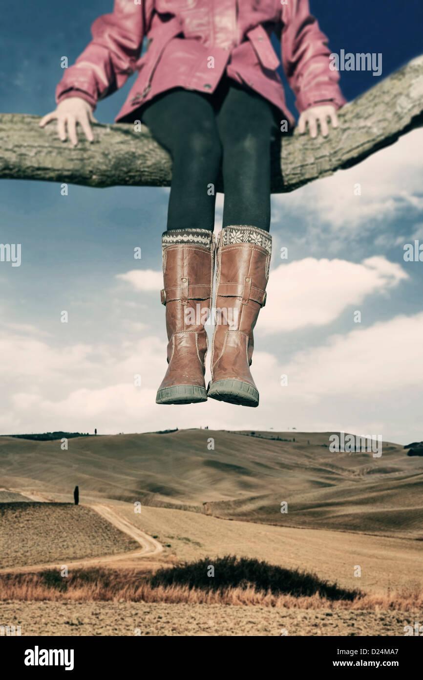 ein Mädchen sitzt auf einem Ast hoch über einem Feld Stockbild