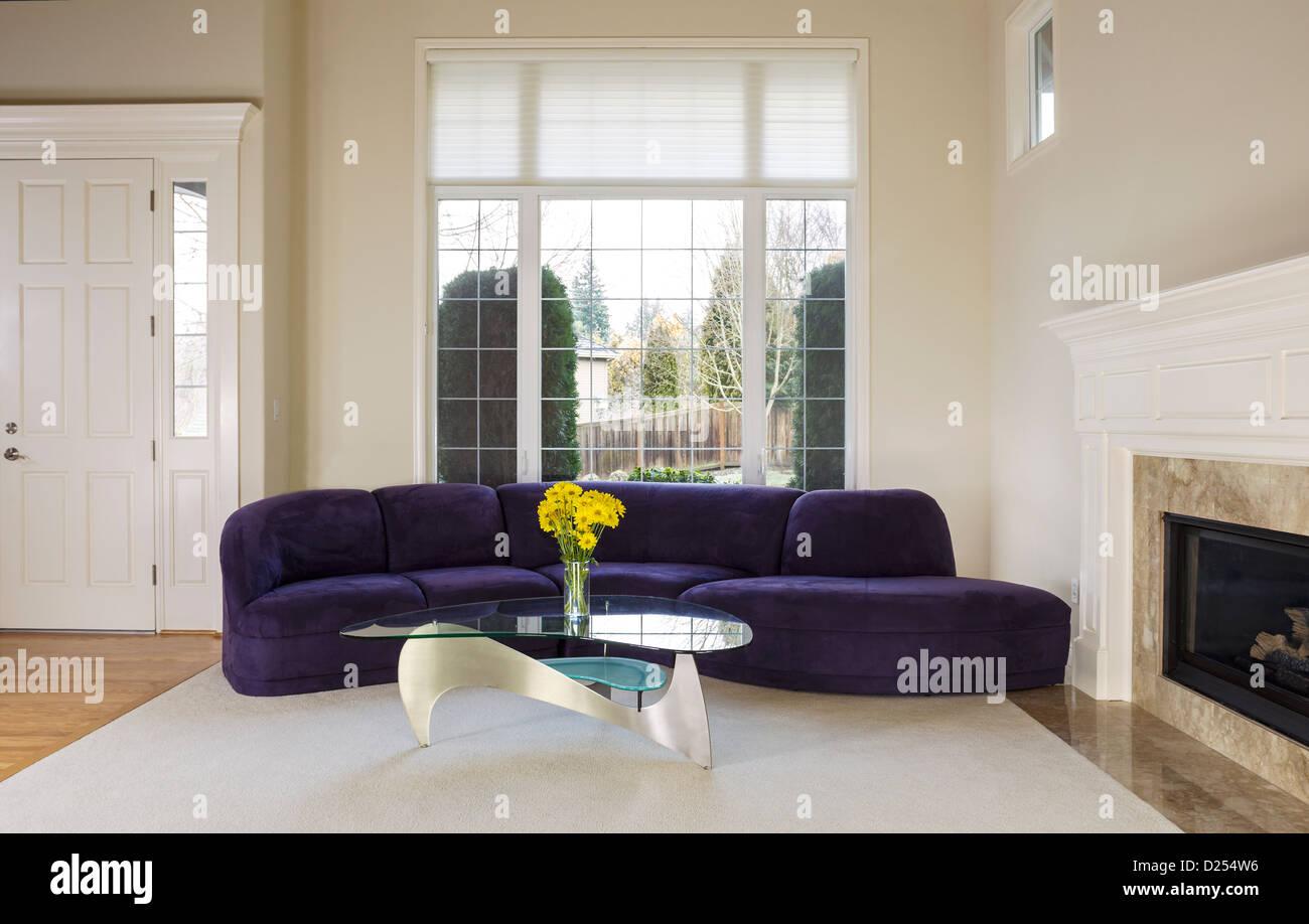 Große Familie Wohnzimmer mit Wildleder Sofa, Glastisch vor großen zweifach verglasten Fenster mit Tageslicht Stockbild