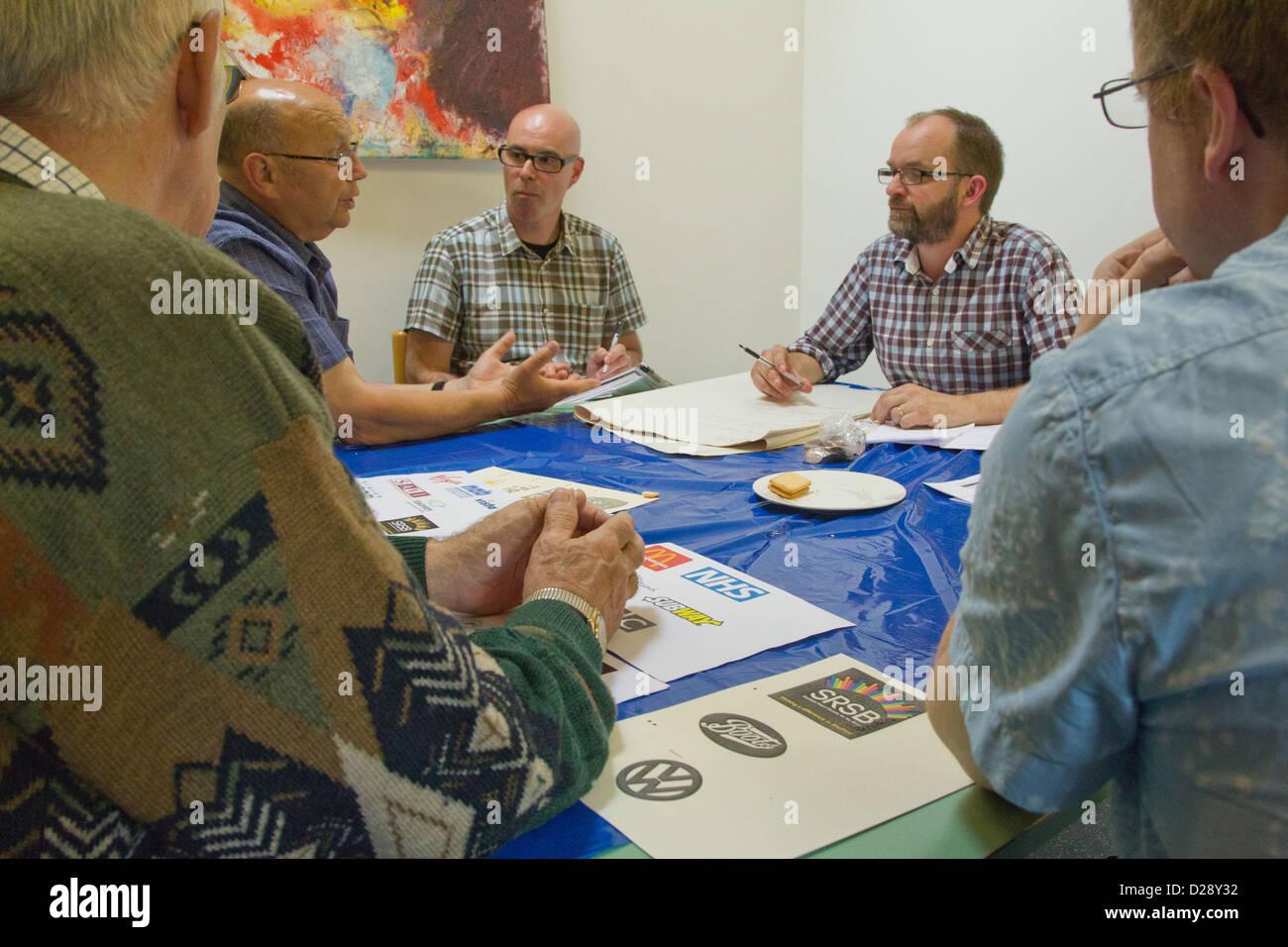 Rücksprache mit Mitarbeitern und freiwilligen Helfern an Nächstenliebe für Menschen mit Sehbehinderungen Stockbild