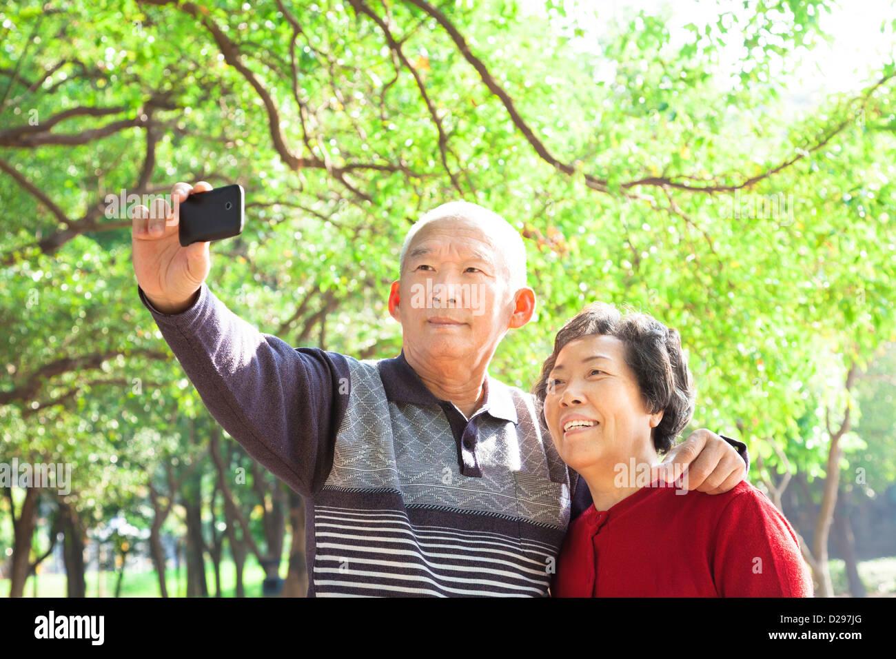 Älteres paar unter Bild von sich selbst im freien Stockbild