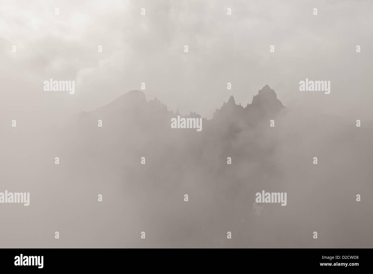 Nebel und Wolken um die 3000 Meter vertikale Trollmauer und die Spitzen Trolltindane, im Tal Romsdalen, Østfold, Stockbild