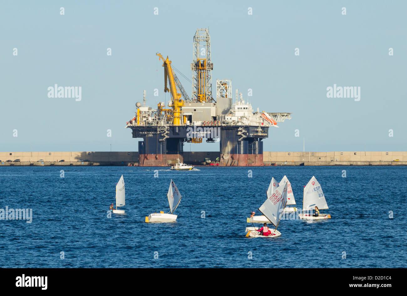 Optimist-Jollen Segeln vor Insel Innovator halb versenkbaren Bohren rig im Hafen von Las Palmas auf Gran Canaria Stockbild