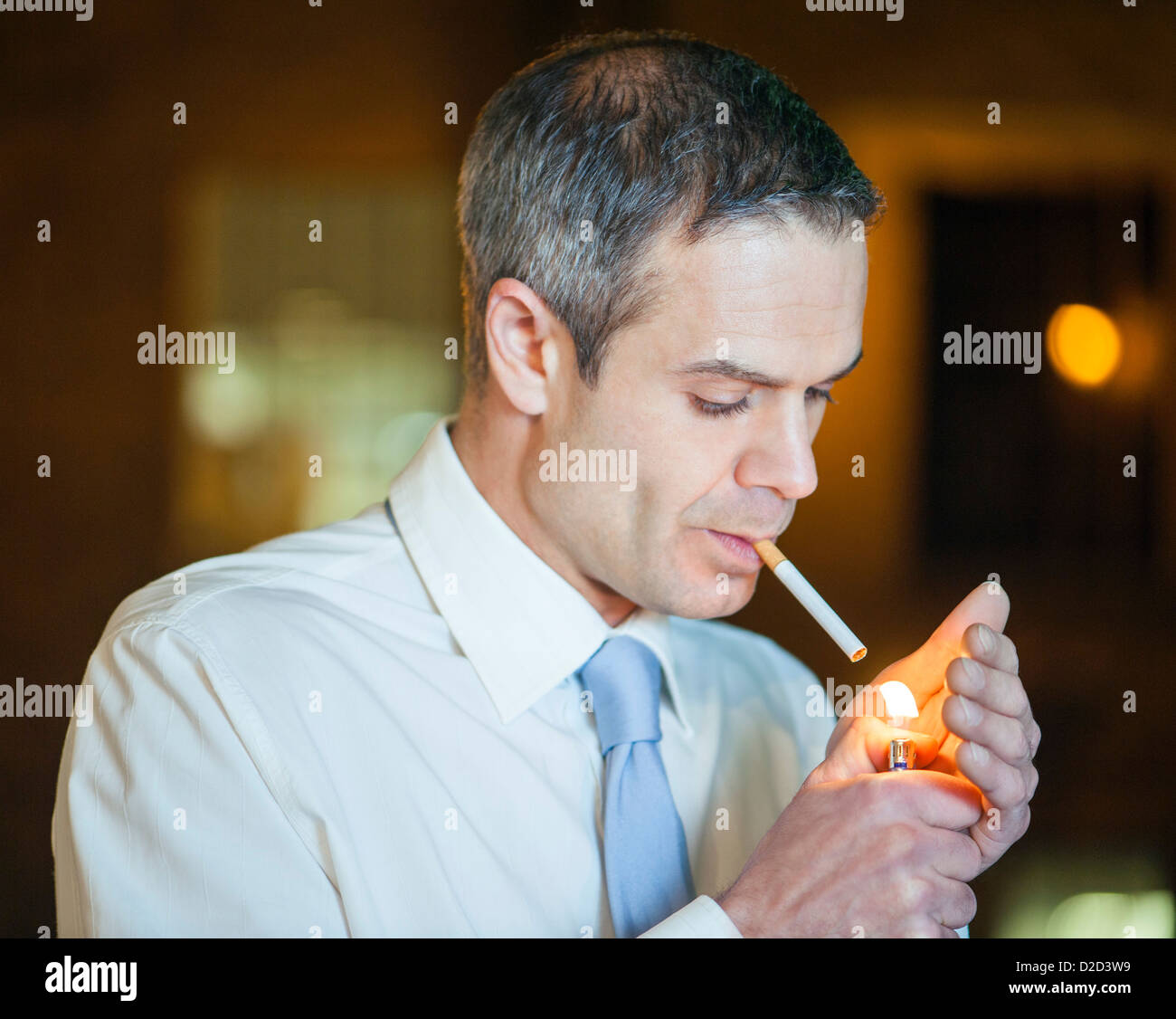 MODEL Release Mann zündet sich eine Zigarette Stockfoto