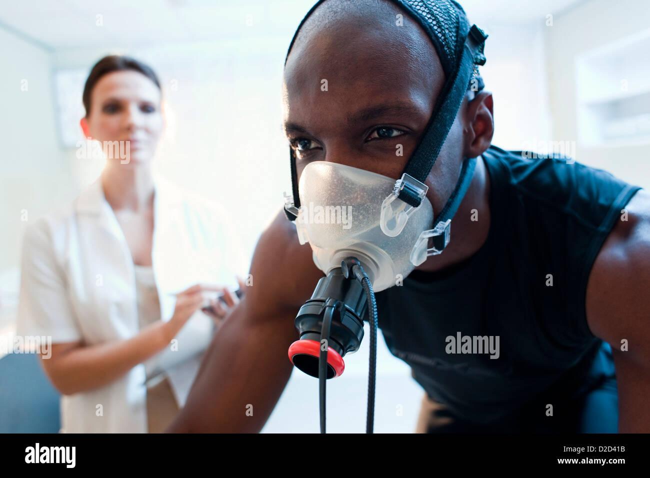 MODEL Release Leistungstests Athlet einen Heimtrainer zu reiten, während seine Leistung und Sauerstoffverbrauch Stockbild
