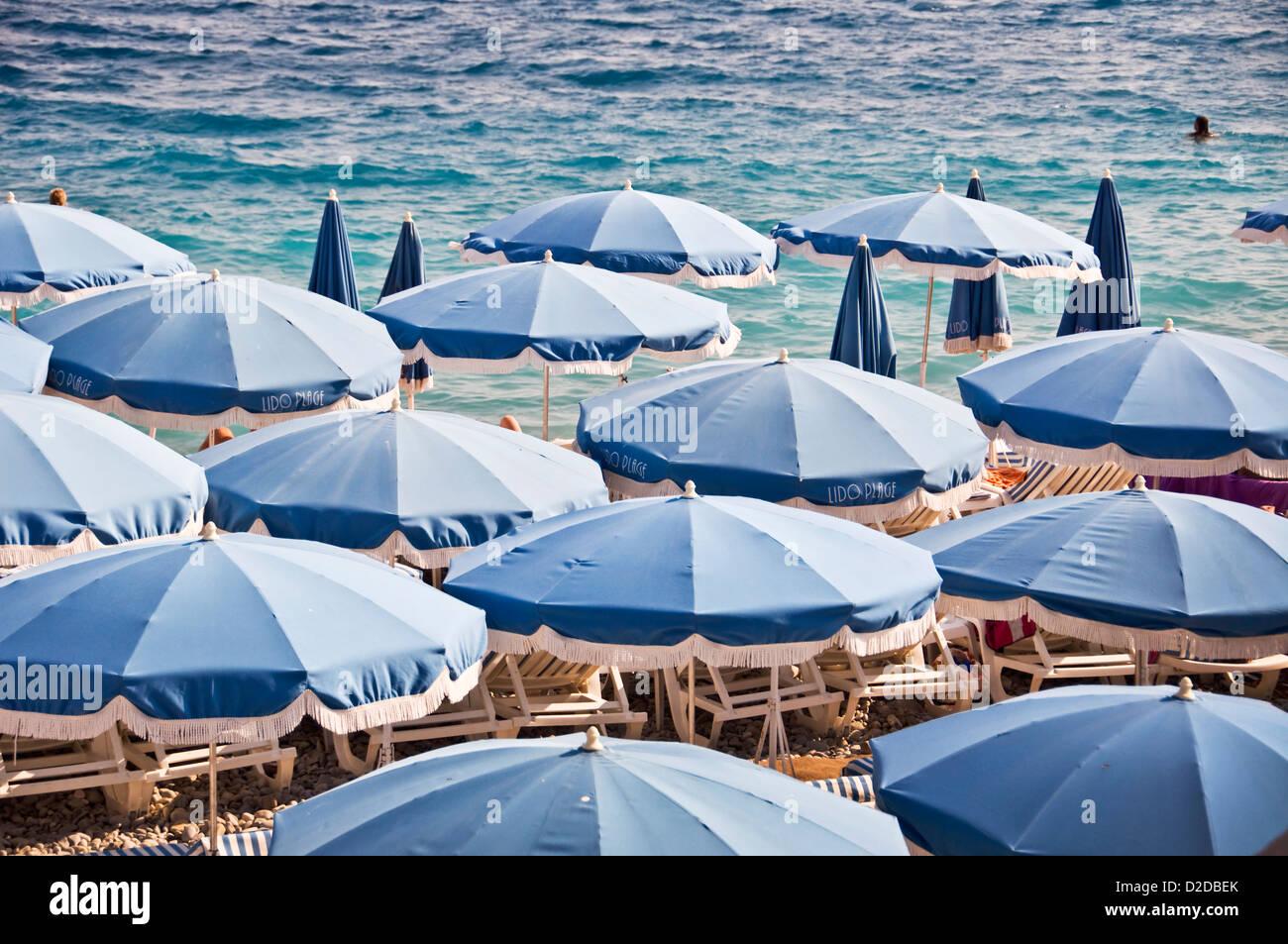 Privatstrand mit blauen Sonnenschirmen, Meer im Hintergrund Ansicht von oben - Nizza, Frankreich Stockbild