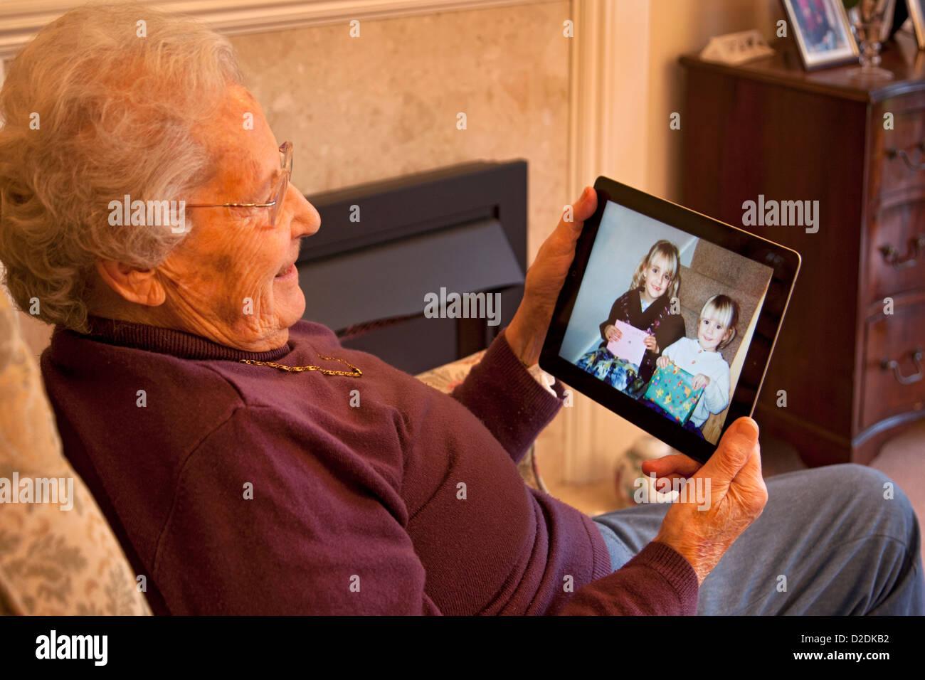 Ältere Frau Rentner mit Brille auf Apple Ipad Tablet zu Hause relaxen am Stuhl Blick auf Foto der Enkelkinder Stockbild