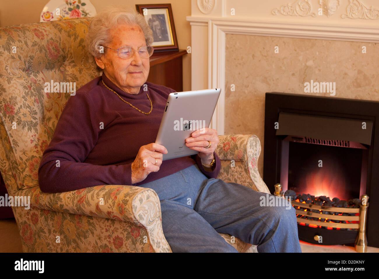 Ältere Frau Rentner mit Brille entspannen Sie sich auf den Stuhl und las ihr Ipad tablet Stockbild