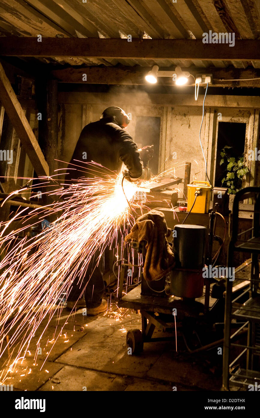 Ein Mann mit elektrischen Scheibe Fräser Schleifer schneidet Metall ...