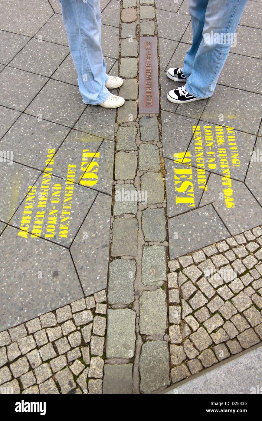 Zwei Beinpaare einander zugewandt auf der nach unten gebracht Berlin Mauer in Berlin, Deutschland. Stockbild