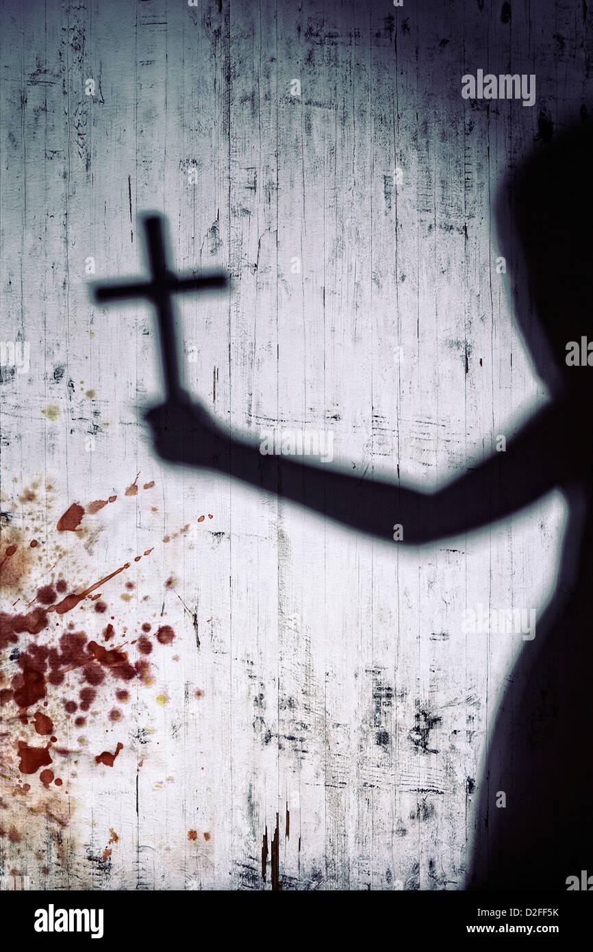 Schatten einer Person mit einem Kruzifix auf einer blutigen weißen Wand Stockbild