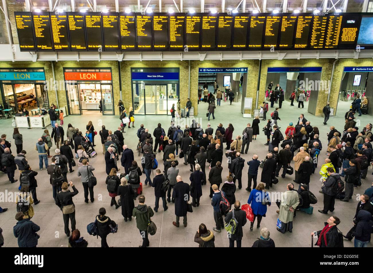 Die Leute am Bahnhof Kings Cross, London, UK - mit Blick auf die Abfahrt Platten im abendlichen Hauptverkehrszeit Stockbild