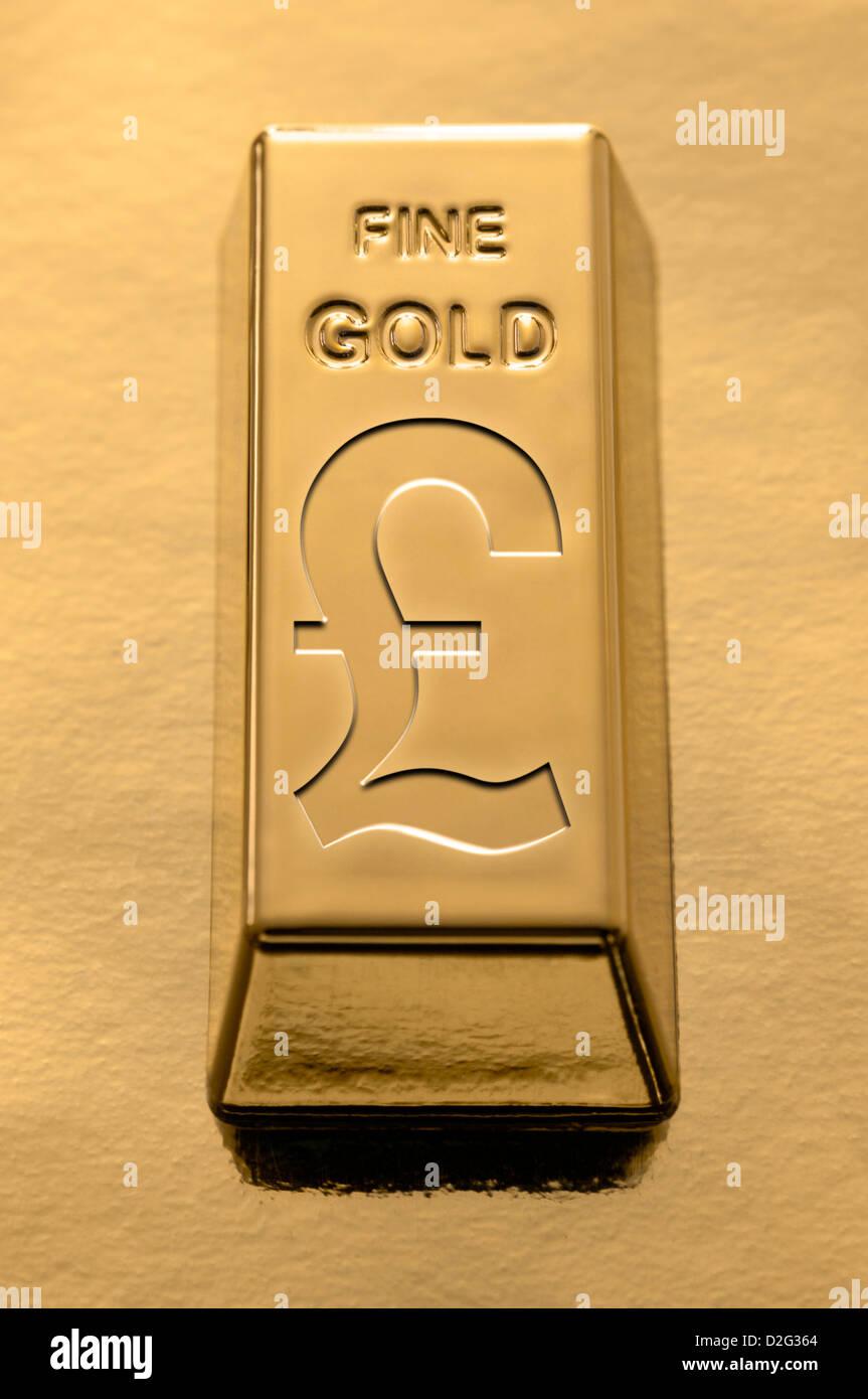 Goldbarren mit einem Sterling Pfund-Symbol auf Goldgrund auf ihr eingeprägten Stockbild