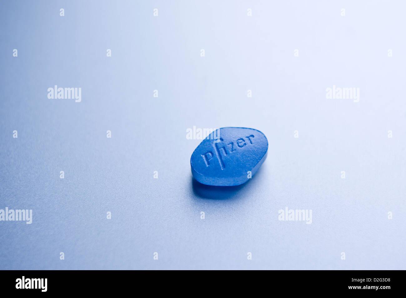 Nahaufnahme Detail von einer 100mg Sildenafil Citrat Pfizer Viagra Pille auf silbernem Hintergrund Stockbild