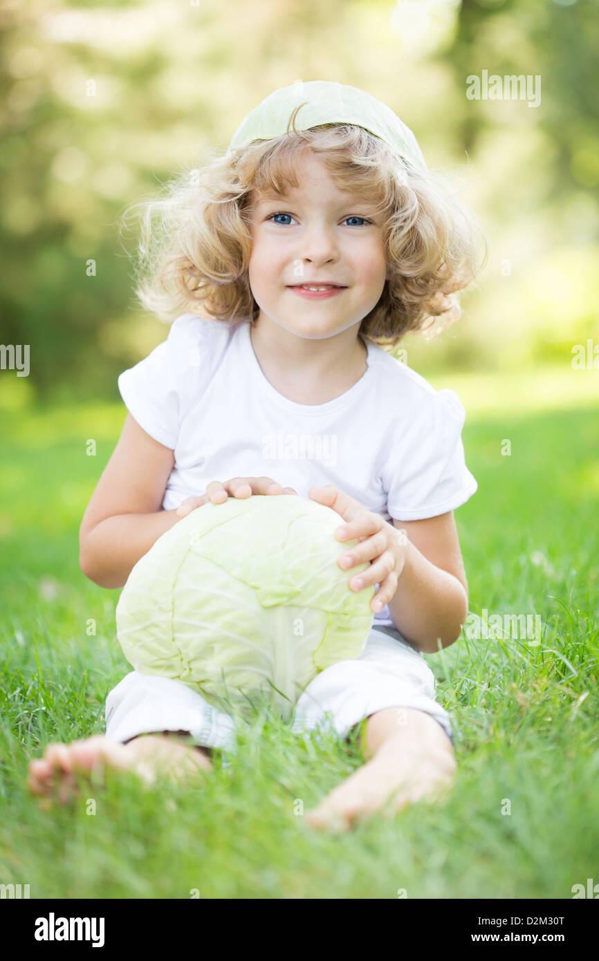 Glücklich lächelnde Kind mit Kohl sitzt auf dem grünen Rasen im Frühlingspark. Gesunder Lebensstil Stockbild
