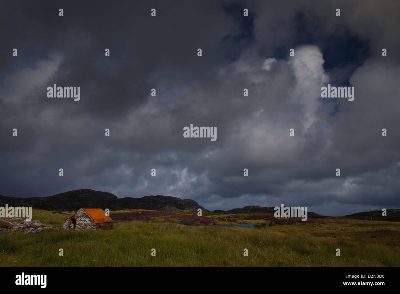 Kleinen Steinhütte neben ein Loch auf North Uist in den äußeren Hebriden Stockfoto