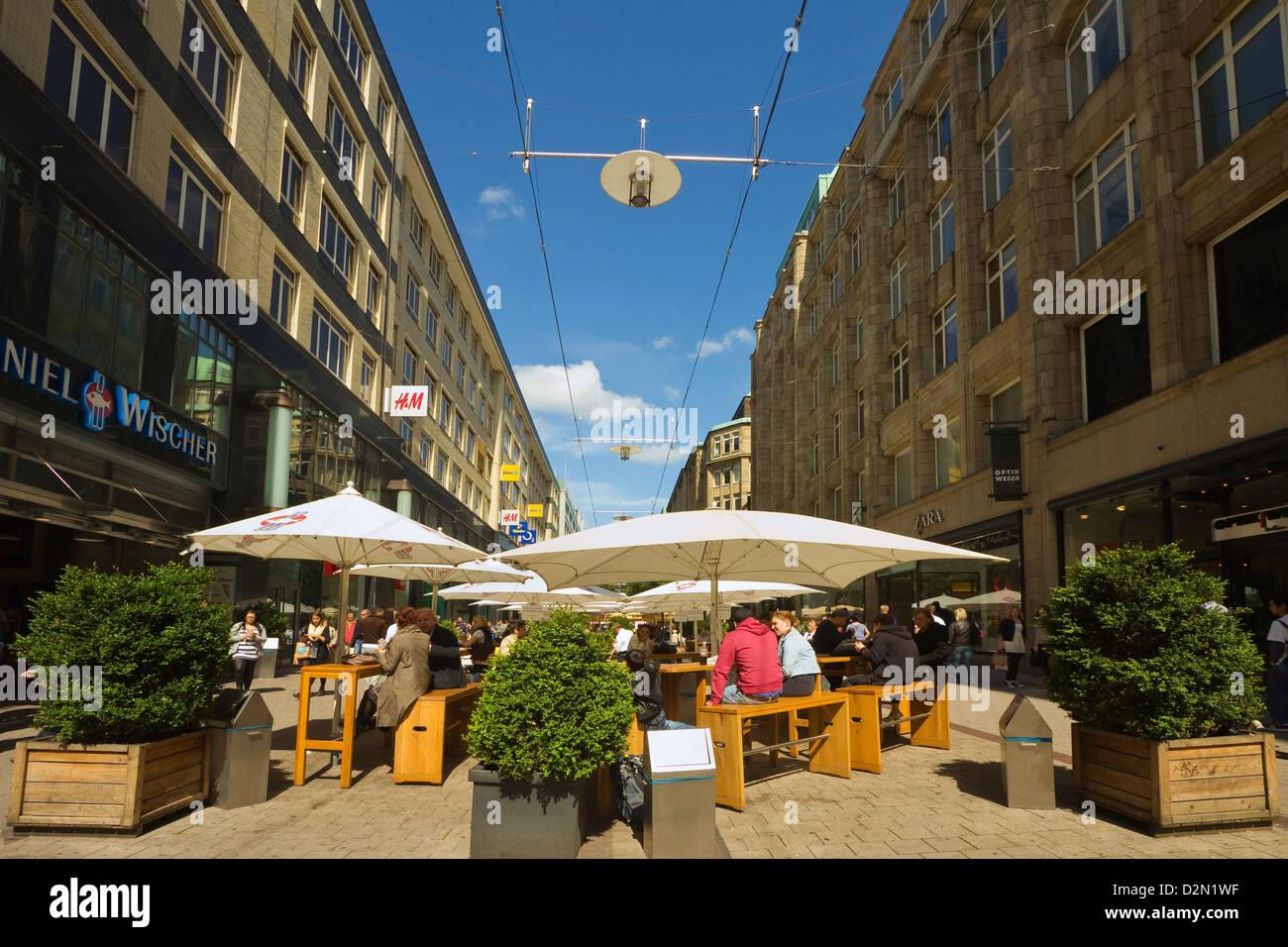 Leute sitzen im Freien unter Sonnenschirmen vor Restaurant auf verkehrsberuhigten shopping Street, Spitalerstraße, Stockbild