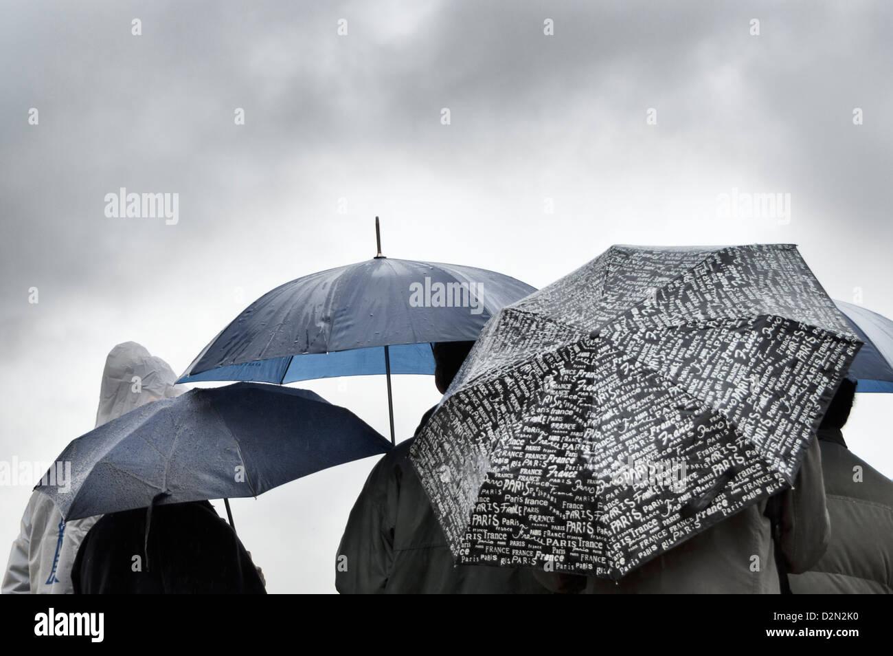 Eine Gruppe von Menschen, die Zuflucht vor dem Regen unter Sonnenschirmen in Paris Stockbild