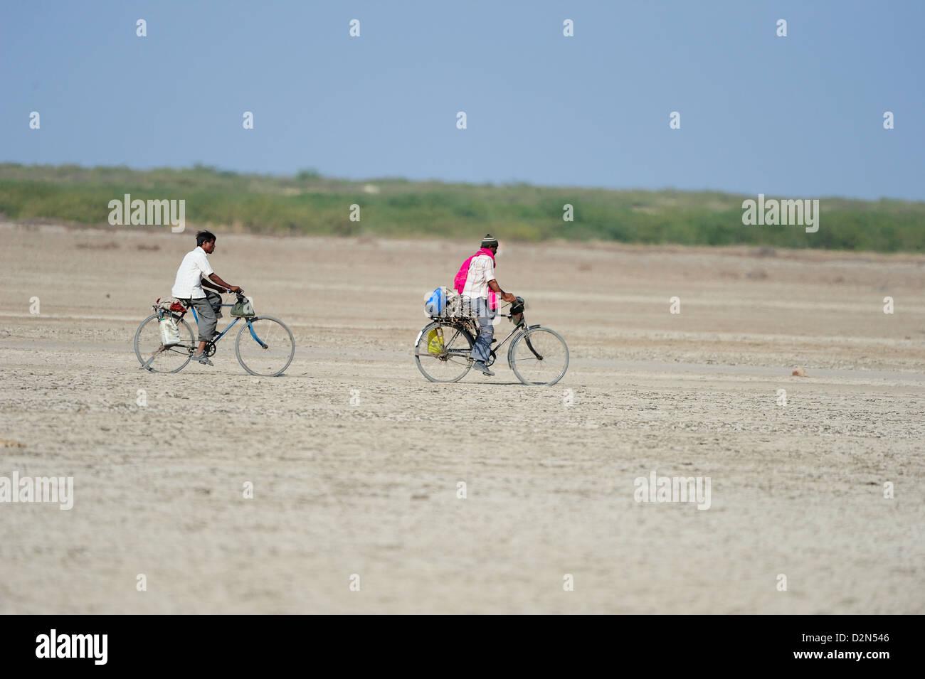 Im ländlichen Indien gehen Männer auf Fahrrädern zu den weit entfernten Städten für Arbeit, Stockbild