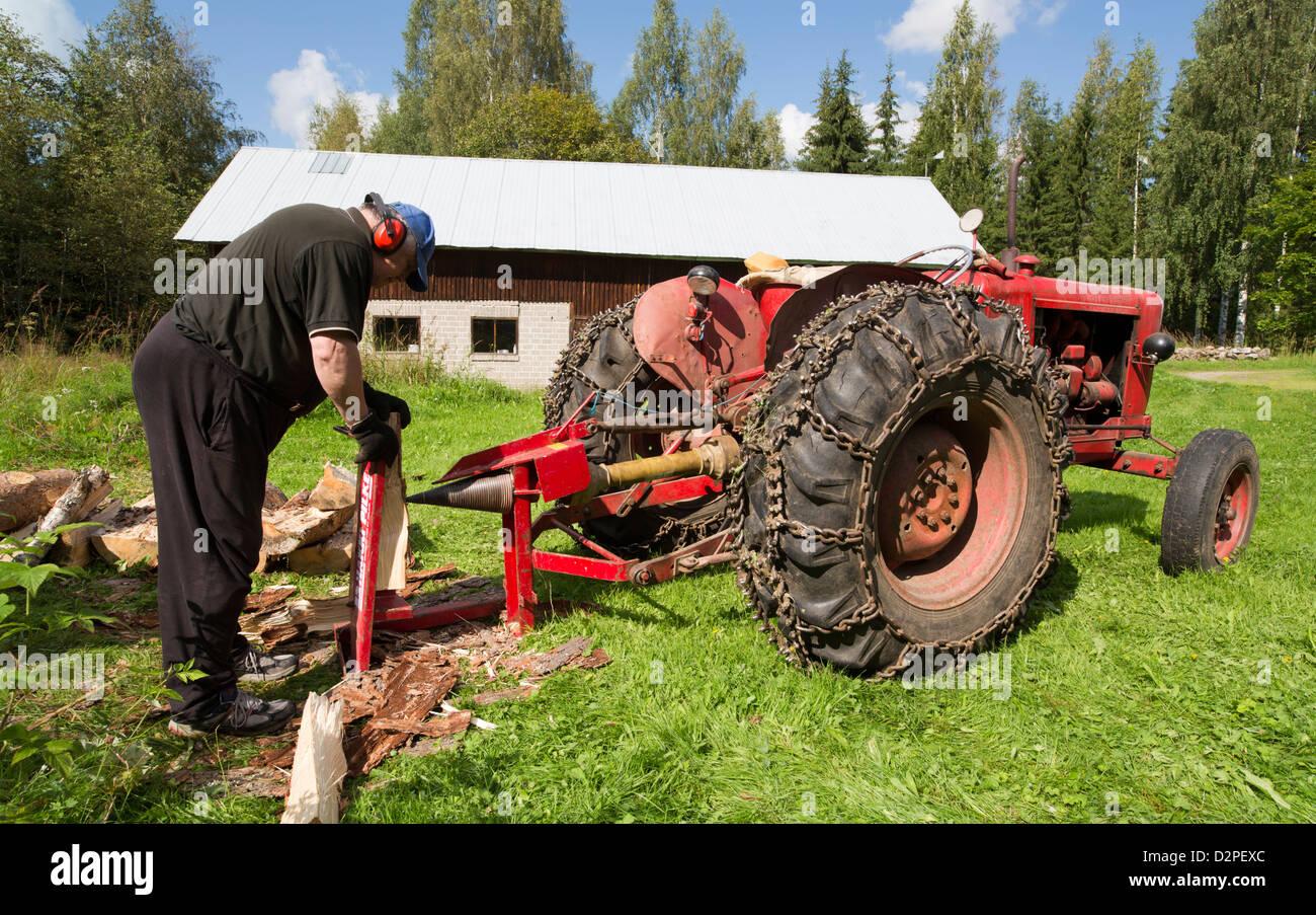 Älterer mann machen brennholz mit traktor angetrieben schraube