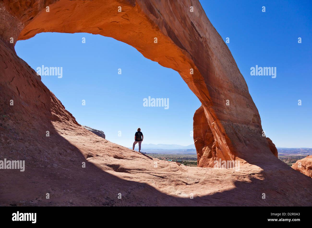 Einsame Touristen Wanderer am Wilson Arch, in der Nähe von Moab, Utah, Vereinigte Staaten von Amerika, Nordamerika Stockbild