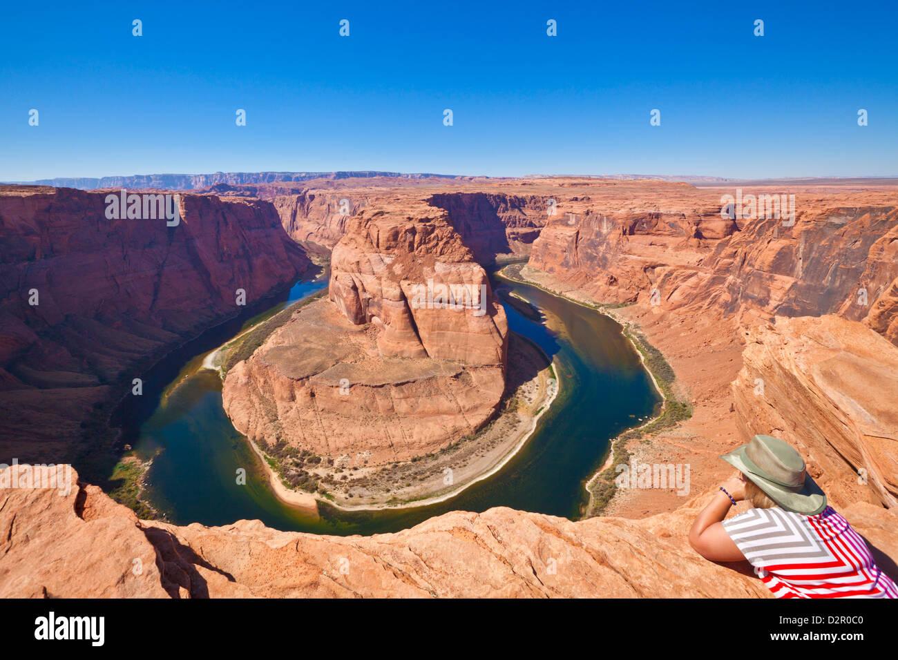 Touristen, die mit Blick auf Horseshoe Bend auf dem Colorado River, Page, Arizona, Vereinigte Staaten von Amerika, Stockbild