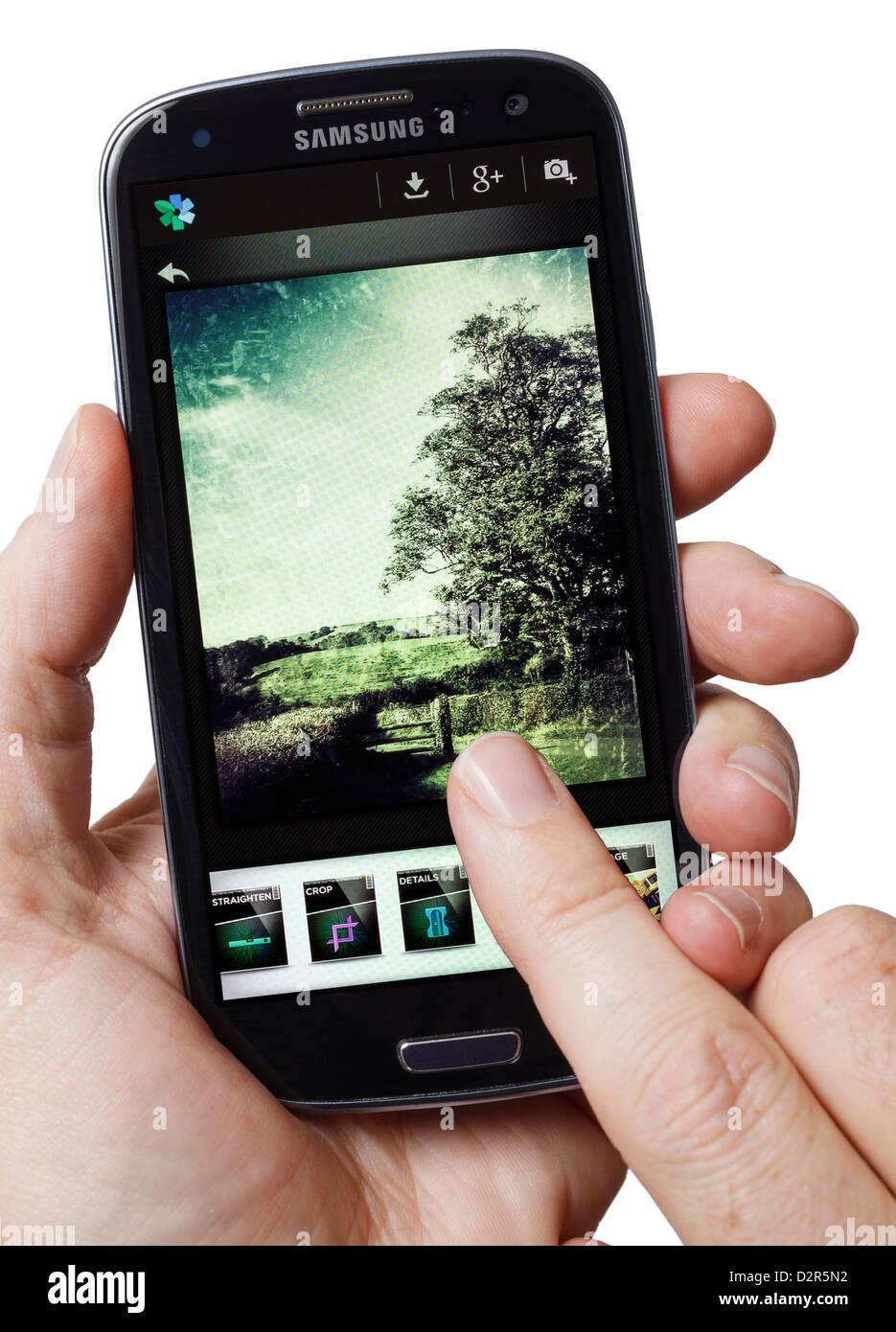 Mit einem Foto manipulation App auf einem Smartphone smart phone mobile phone Stockbild