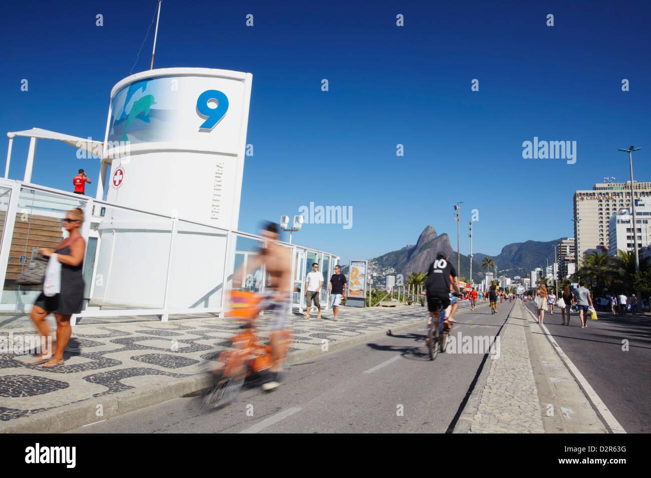 Menschen, Radfahren und Wandern entlang der Fußgängerzone am Sonntag, Ipanema, Rio De Janeiro, Brasilien, Stockbild