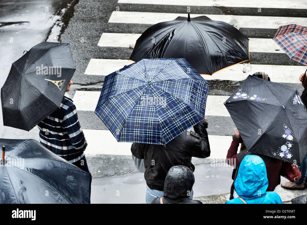 Fußgänger mit Schirmen durch eine Überfahrt auf einer Stadtstraße im Regen Stockbild