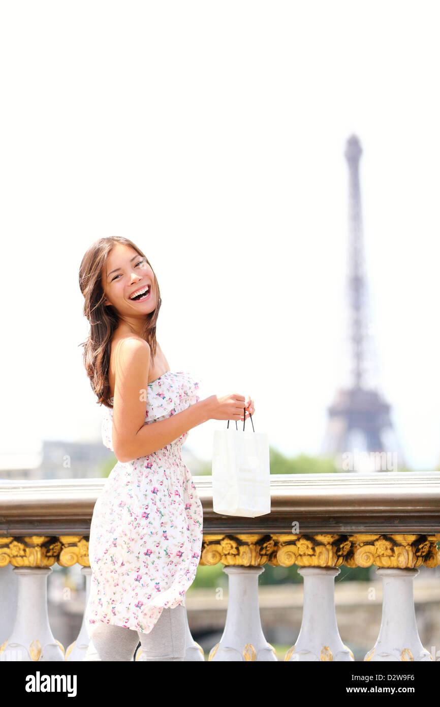 Schöne fröhliche junge multirassische Frau genießen ihre Paris-Reise mit Eiffelturm im Hintergrund Stockbild