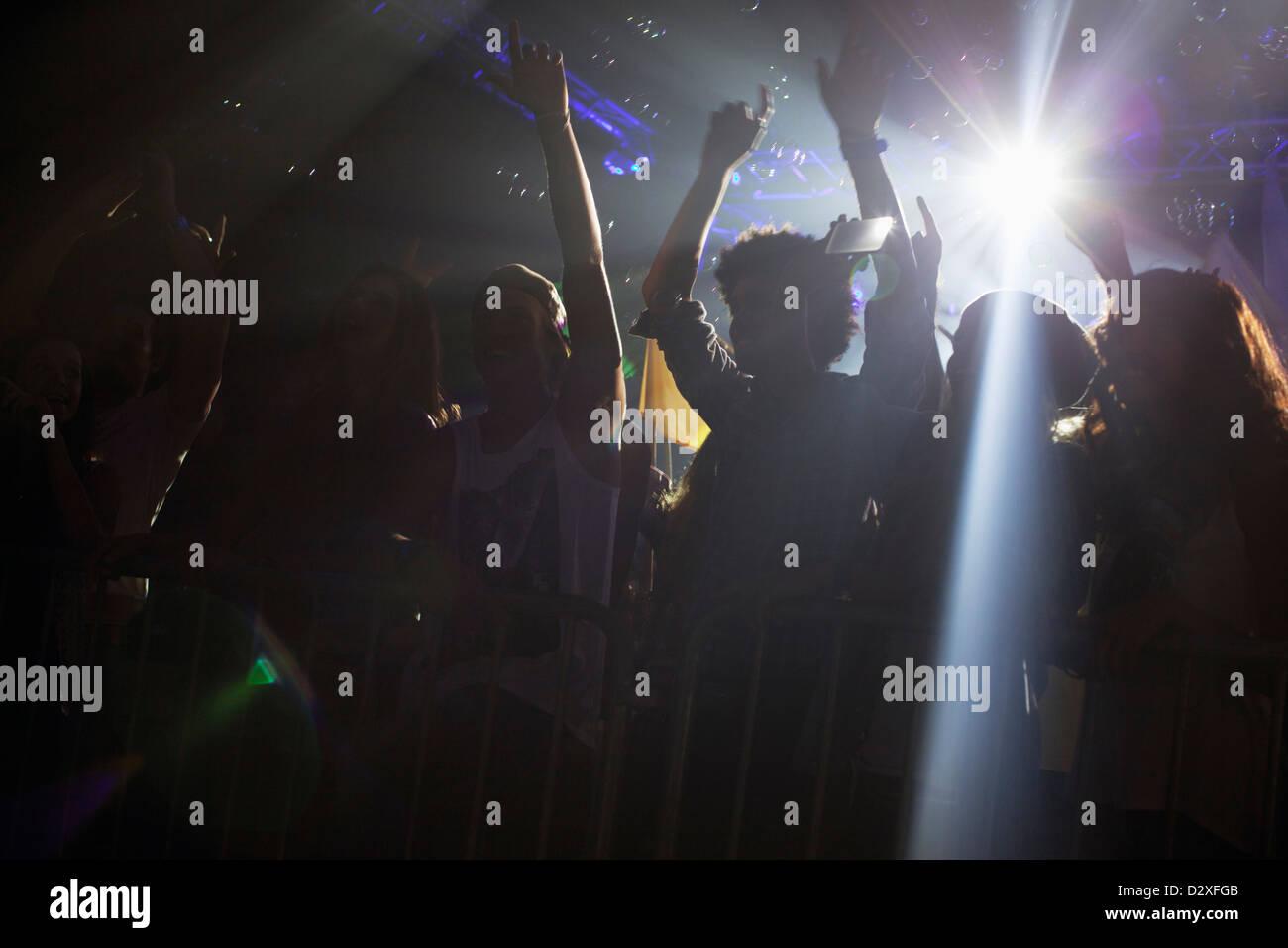Scheinwerfer über Silhouette der Menge jubeln beim Konzert Stockbild