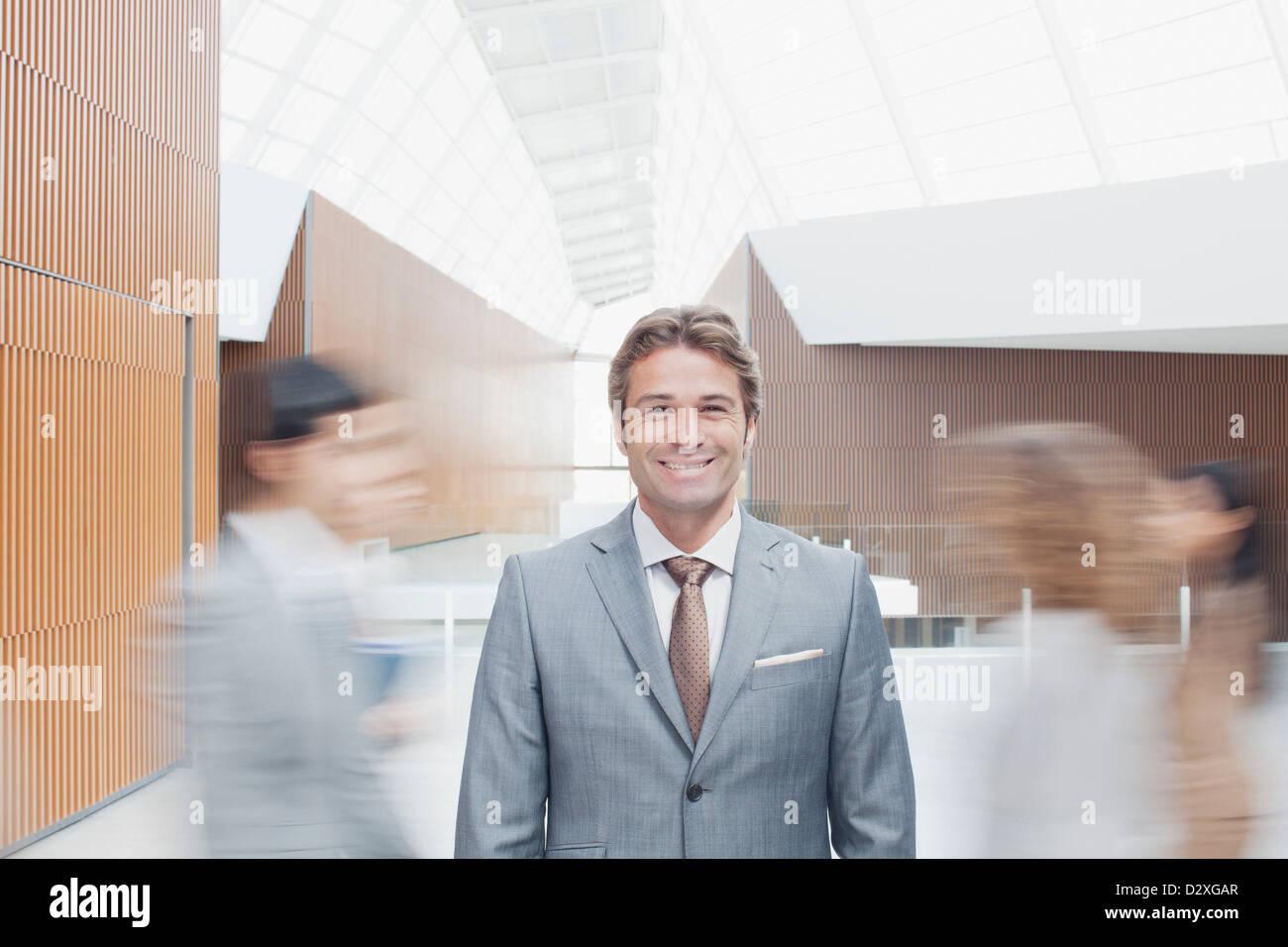 Porträt von zuversichtlich Geschäftsmann mit Kollegen in Lobby durch Rauschen Stockfoto