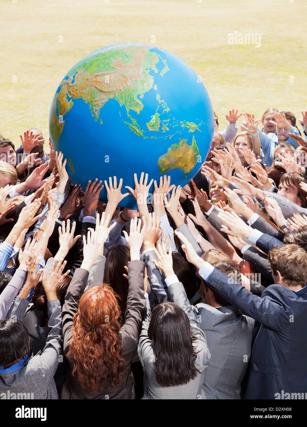 Masse der Geschäftsleute erreichen für globe Stockbild