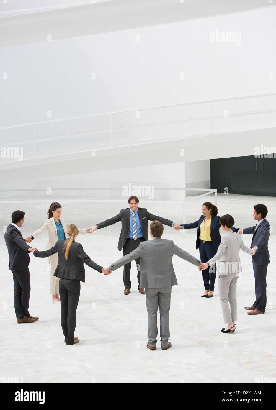Geschäftsleute, die Hand in Hand im Kreis Stockbild